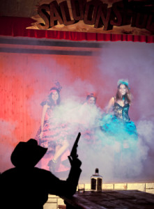 Tree young woman in smoke dancing before shooting cowboy